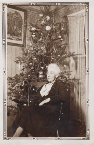 Jane Ellen Hagell age 78 sits in front of a Christmas tree