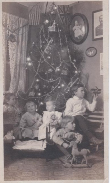 Old black and white photo of five children in front of a Christmas tree